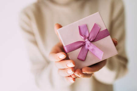 Female hands holding pastel coloured present with pink ribbon. Festive backdrop for holidays: Christmas, New Year, Birthday, Valentines day. Stock Photo