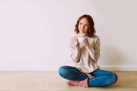 Dreaming young red haired woman sitting on the floor on a white blank background. Female model smiling looking up, holding a cup with hot coffee.