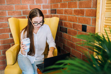 Young successful businesswoman in glasses working on a black laptop in a coffee shop, holding coffee cup and typing. Фото со стока
