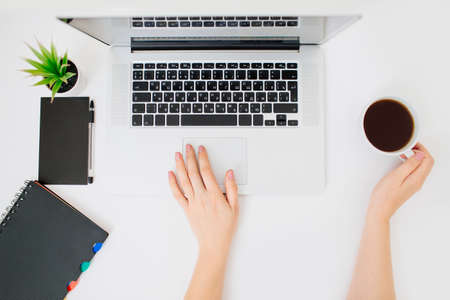 Overview of female hands scrolling laptop touch pad. Coffee, plant, notebook and pen beside. Flat lay styled office space.