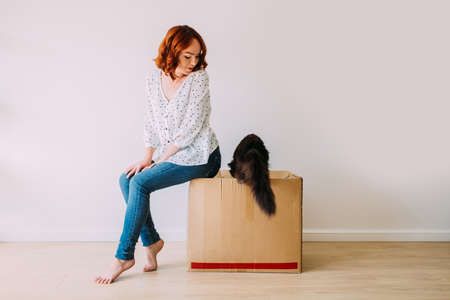 Young girl moving into the new apartment. Sitting on a carton box on a white empty wall background, black fluffy cat jumping inside the box.