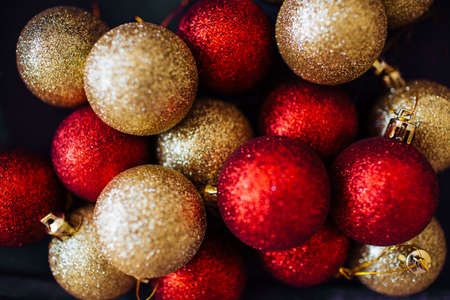 Red and golden Christmas balls decoration top view. New year greeting card. Festive backdrop.