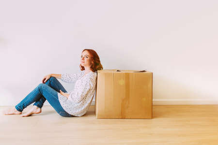 Young attractive girl moving into the new apartment. Sitting on the floor with big carton box in an empty room on a white wall background.