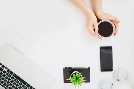 Female hands holding a mug with black coffee. Workspace with laptop, mobile phone and headphones. Flatlay photo. Home office concept. Copy space.
