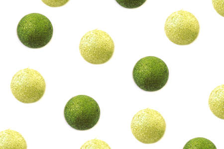 Shiny golden and green balls Christmas pattern isolated on white background. Top view festive background. Фото со стока