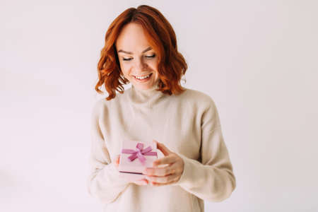 Young birthday girl smiles, holding a pastel coloured gift box with pink ribbon. Happy woman, peeking inside a gift box.