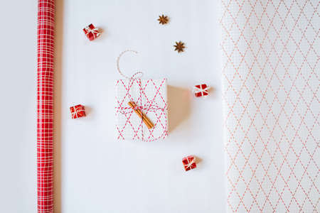 Christmas concept. Decorations, gift paper, wrapped gift on white background. Festive flatlay with copy space.