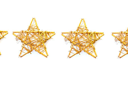 Xmas pattern. Decoration with multiple vintage golden stars in a row, isolated on white background. Top view, copy space. Holiday backdrop. Фото со стока