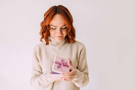Young girl with festive mood gently smiles, holding a pastel coloured pink gift box with a ribbon. Happy woman, peeking inside a gift box.