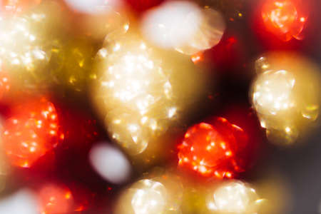 Blurred subtle bokeh with sparkling golden and red festive circles. Festive or Christmas background. Фото со стока