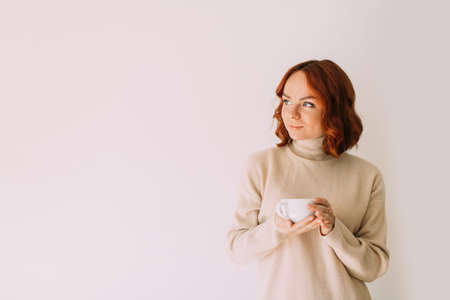 Lifestyle portrait of red haired beautiful woman sipping coffee from a white mug, wearing cozy sweater. Looking aside. Copy space.