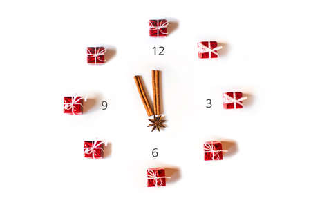 New Year clock concept. Watch face represented with small Xmas gifts and sticks of cinnamon, isolated on white background. Flat lay with copy space.