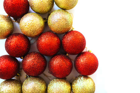 Close up of red and golden Xmas balls decoration pile. Overview of shiny baubles. Festive backdrop. Фото со стока