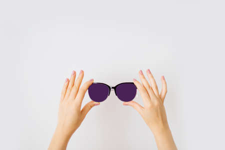 Female hands holding stylish sunglasses with dark purple lens isolated on white background. Фото со стока