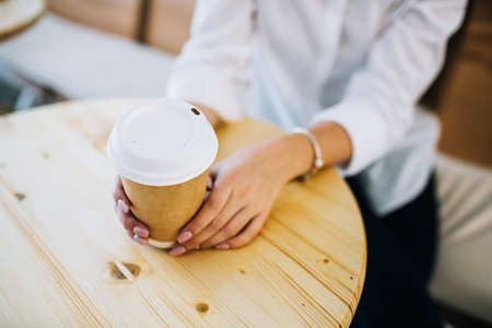Female hands holding recyclable paper coffee cup at a cafe. Top view with light wooden table. Фото со стока