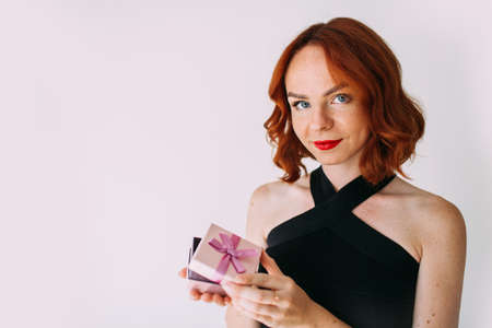 Portrait of a happy smiling girl in an elegant black dress holding pink present box with a ribbon, isolated on white background. Фото со стока