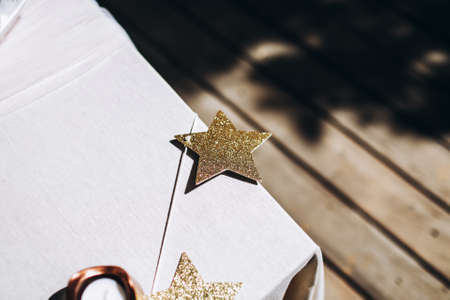 Birthday sparkling star decoration on a table edge. Sparkling golden colored garland for birthday celebration. Copy space.