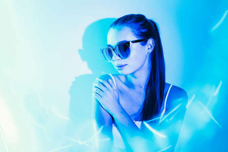 Night portrait of a young attractive girl with reflection in sunglasses in blue neon light flashes. Copy space.