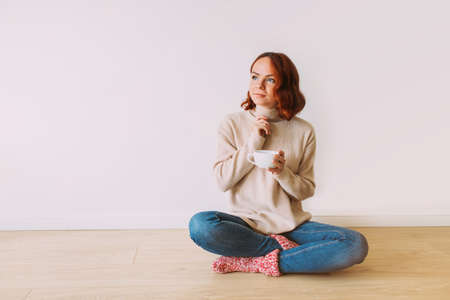Dreaming young red haired girl sitting on the floor on a white blank background. Female model looking up, holding a mug with hot coffee. Copy space. Фото со стока