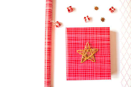 Flat lay with red gift box, wrapping paper and cute festive details, isolated on white background. Christmas and New Year festive concept. Copy space.
