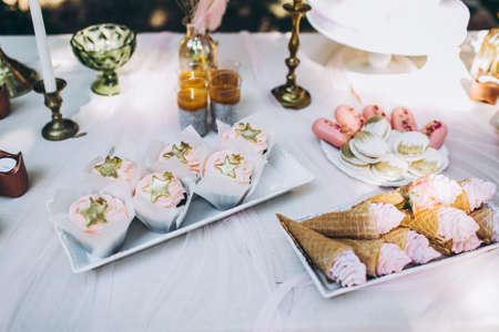 Tasty birthday cupcakes of pink pastel color with stars on top, and other sweet confections, lying on the table. Festive composition. Фото со стока