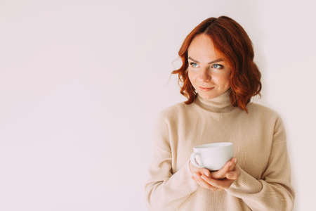 Lifestyle image of red haired beautiful girl sipping coffee from a white mug, wearing cozy sweater of a pastel color. Looking aside. Copy space.