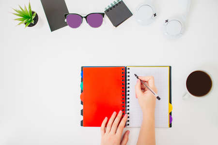 Flatlay with female hands writing notes ob a blank paper. Minimalistic office work place. White background, cup of black coffee and stationery beside.