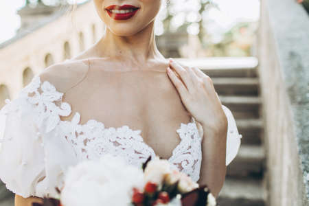 Wedding portrait of a bride, holding red and white flowers in hand. Close up, red lips, no face seen. Фото со стока