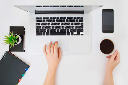 Top view of female hands working with a laptop. A cup of coffee, notebook and mobile phone beside. Flat lay styled office place. Фото со стока