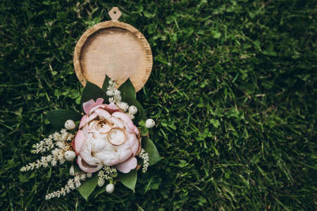 Round wooden box with tender flowers, greenery, roses and golden wedding rings, lying on a fresh green grass. Фото со стока