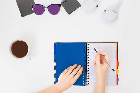 Flatlay with female hands writing in a notebook. Minimal office workspace. White background and cup of black coffee beside.