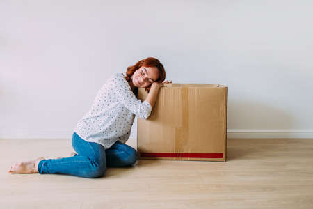 Attractive girl moving into the new apartment. Sitting on the floor with carton box in an empty room, smiling. Daydreaming, white wall background.