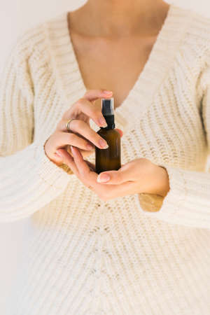 Woman holding a bottle with natural skincare product. Cosmetic and beauty concept. Blank dark bottle. Close up with a product and female hands.