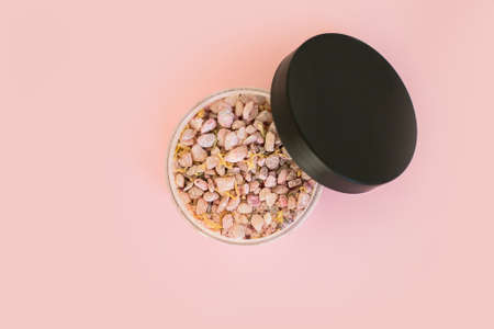 Natural sea salt mineral grains in a round container. Overview on pink background. Flat lay with beauty product.