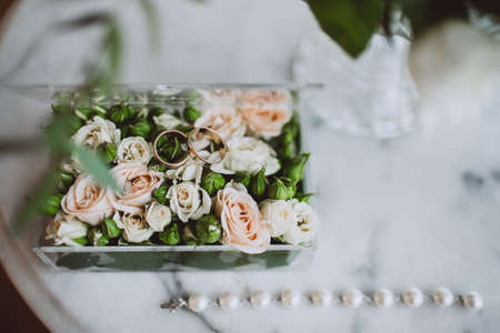 Wedding rings on a floral surface with roses and green blossom. Transparent box with jewelry and flowers, lying on a white marble table.