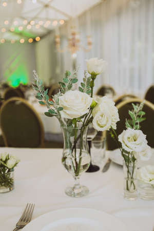 Festive dinner table, decorated with bunch of white roses. Table serving at the party. Flowers in transparent vases as decoration.