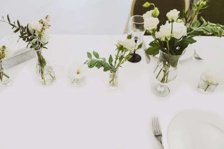 Festive dinner table concept. Top view at the table serving. White roses in transparent vases as decoration. A plate with fork in the corner.