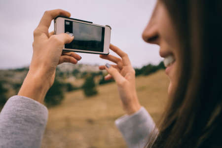 Image of a young smiling girl, holding mobile phone with one hand, taking a picture in the nature.