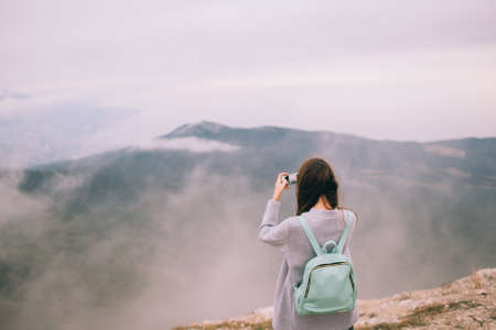Young girl with no face seen taking picture with mobile phone, standing on the edge of a mountain.