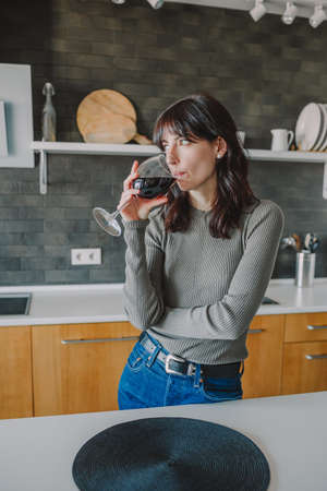 Portrait of young attractive girl enjoying a glass of red wine in the cozy kitchen at home.