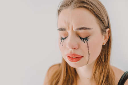Close up portrait of young girl, desperately crying with her eyes closed and mascara running down her cheeks.