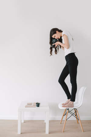 Young female photographer, taking pictures at home.