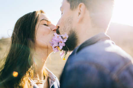 Close up of a loving couple kissing outside in the sunshine, cute flowers in the mans beard.