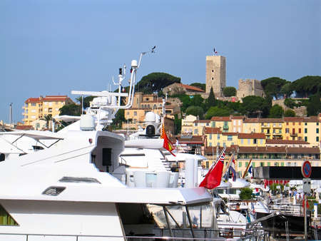 At cannes yacht port. Castle and compacted small houses in the background and empty blue sky.