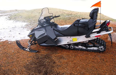 Illustration of a black snowmobile whit orange flag near melted snow