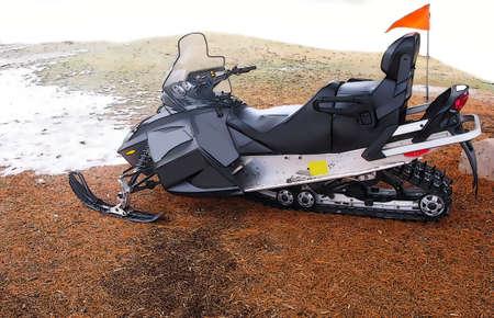 Illustration of a black snowmobile whit orange flag near melted snow