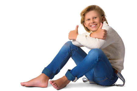 Cute blonde boy or teenager in full length casual style blue jeans posing isolated on white.