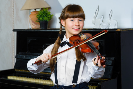 Cute little girl playing violin and exercising indoor.