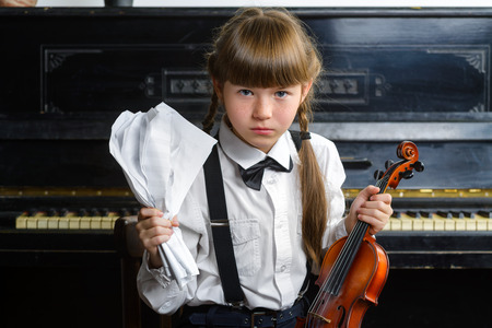 helplessness: distraught and distressed girl clutching her head and holding a violin.