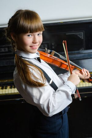 kids studying: Cute little girl playing violin and exercising indoor.
